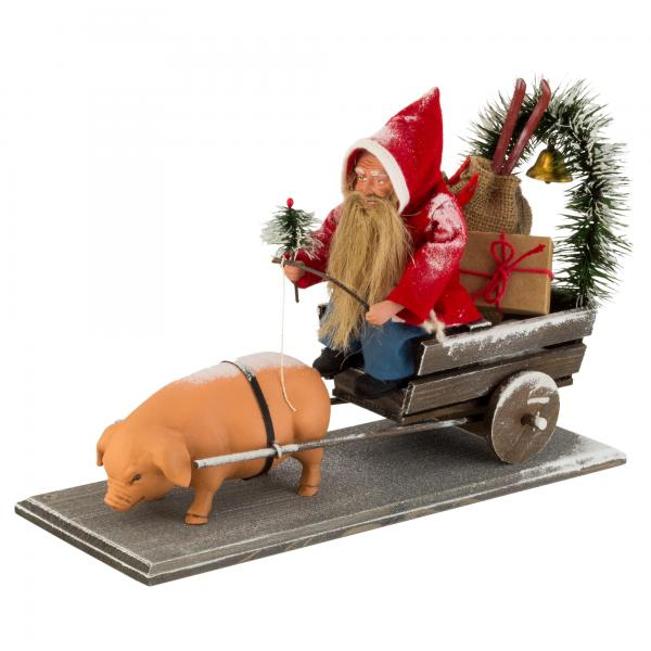 Christmas cart with lucky pig (feather tree garland, brass bell, sack with toys, gift package) on wooden board