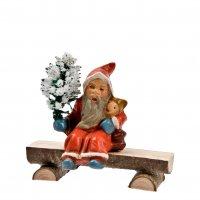 Miniatur - Weihnachtsmann auf Holzbank sitzend